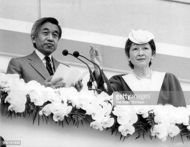 Emperor Akihito addresses while Empress Michiko raises her hand to cover the emperor as a man throws a smoke bomb toward them during the opening...