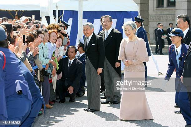 Emperor Akihito and Empress Michiko greet wellwishers who are queuing to sign a book to celebrate the 50th anniversary of their wedding at the...
