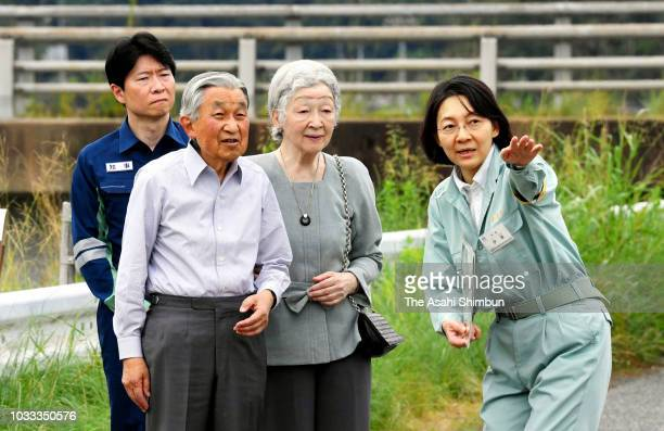 Emperor Akihito and Empress Michiko wave to wellwishers during their visit to the torrential rain hit Mabi area to encourage people on September 14...