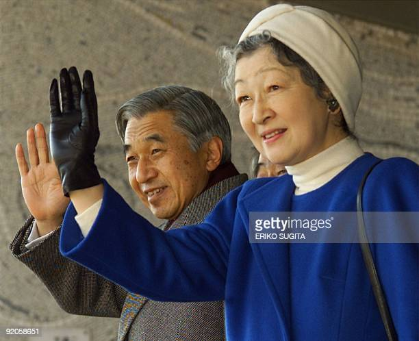 Emperor Akihito and Empress Michiko of Japan wave to soccer fans as they arrive at Tokyo's National Stadium to watch the Emperor's Cup soccer...