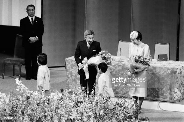 Emperor Akihito and Empress Michiko receive flower bouquets from children during a ceremony marking the emperor's enthronement at Tokyo Bunka Kaikan...