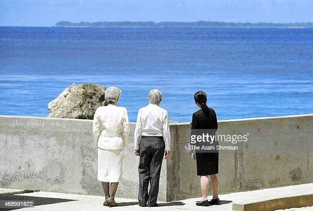 Emperor Akihito and Empress Michiko stand to watch the Angaur Island or Ngeaur Island after offering flowers at the West Pacific Ocean Monument to...