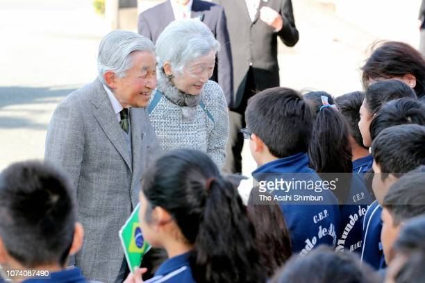 Emperor Akihito and Empress Michiko talk with children on arrival at the Hamamatsu Foreign Resident Study Support Center on November 28 2018 in...
