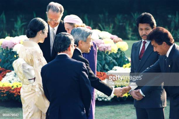 Emperor Akihito and Empress Michiko talk with guests during the garden party celebrating his Enthronement at the Akasaka Imperial Garden on November...