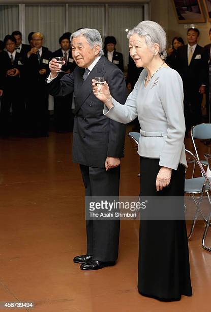 Emperor Akihito and Empress Michiko toast during a tea party to celebrate their 80th birthday hosted by the Imperial Household Agency at the Imperial...