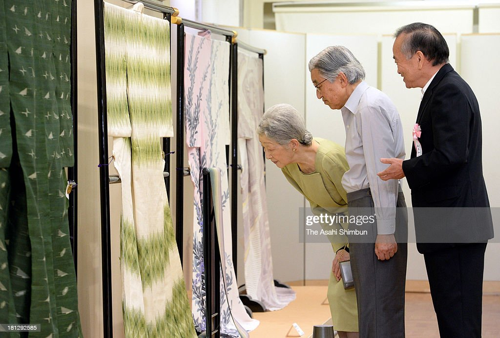 Emperor Akihito (C) and Empress Michiko (L) visit the Japanese Traditional Art Crafts Exhibition at Mitsukoshi Department Store on September 20, 2013 in Tokyo, Japan.