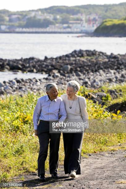 Emperor Akihito and Empress Michiko walk along the coast of Futatsuishi on August 4 2018 in Rishirifuji Hokkaido Japan