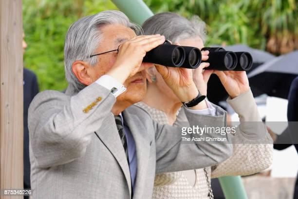 Emperor Akihito and Empress Michiko watch through binoculars during their visit to Yurigahama Beach at Yoronjima Island on November 17, 2017 in...