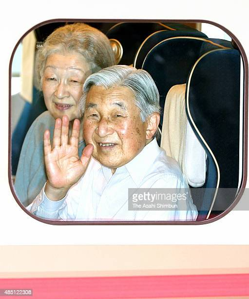 Emperor Akihito and Empress Michiko wave from a Shinkansen bullet train at Tokyo Station on August 22 2015 in Tokyo Japan They will stay Karuizawa...