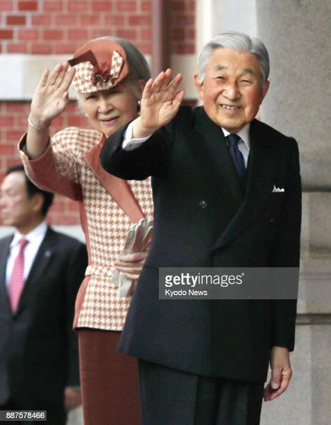 Emperor Akihito and Empress Michiko wave to the crowd at a square in front of JR Tokyo Station that opened on Dec 7 after years of renovation work...