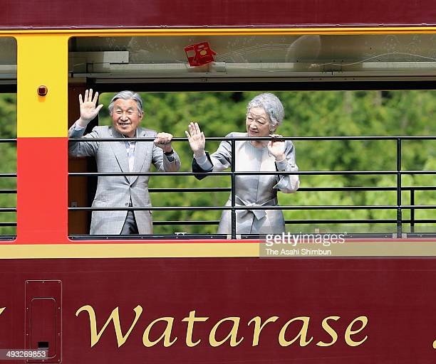 Emperor Akihito and Empress Michiko wave to wellwishers from a carriage of the Watarase Keikoku Railways during their visit on May 22 2014 in Nikko...