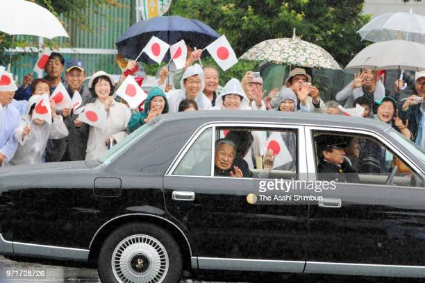 Emperor Akihito and Empress Michiko wave to wellwishers on arrival at the Odaka lifelong learning center on June 10 2018 in Minamisoma Fukushima...