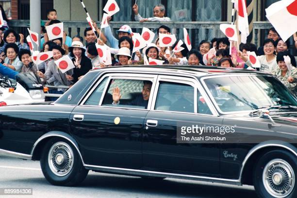 Emperor Akihito and Empress Michiko wave to wellwishers on the way to the Okinawa Children Development Center on April 25 1993 in Okinawa Japan