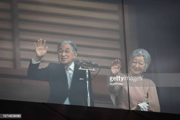 Emperor Akihito and his wife Empress Michiko waves to wellwishers as they appear on the balcony of the Imperial Palace to mark the emperor's 85th...