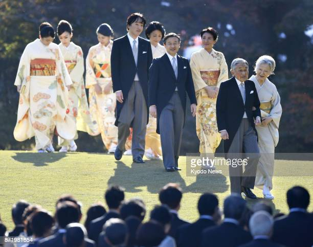 Emperor Akihito Empress Michiko and other imperial family members walk to attend a biannual imperial garden party at the Akasaka Imperial Garden in...