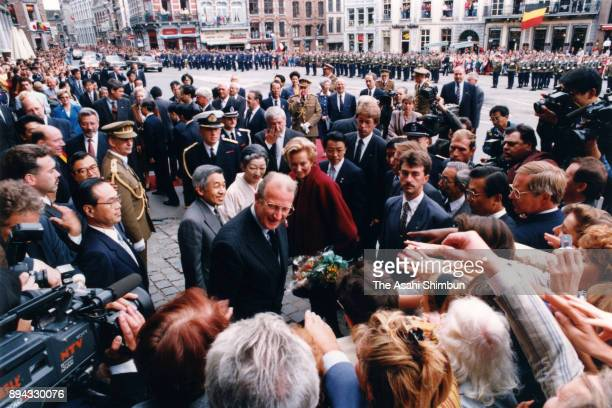 Emperor Akihito Empress Michiko King Albert II and Queen Paola of Belgium are welcomed by residents during their visit to the Mons City Hall on...