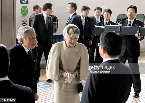 Emperor Akihito escorts Empress Michiko greet while chamberlains hold the boxes to contain the Imperial Regalia at JR Tokyo Station on March 25 2014...