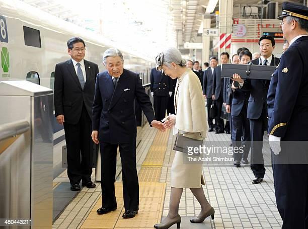 Emperor Akihito escorts Empress Michiko to get a Shinkansen bullet train while chamberlains hold the boxes to contain the Imperial Regalia at JR...