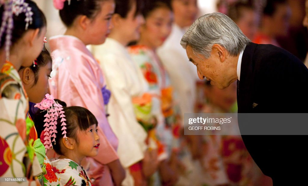 Emperor Akihito of Japan is greeted by a young Japanese