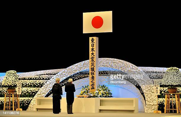 Emperor Akihito, right, and Empress Michiko pray during a memorial service at the National Theater in Tokyo, Japan, on Sunday, March 11, 2012....