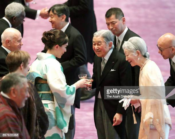 Emperor Akihito talks with guest along with Empress Michiko during a tea party celebrating his 84th birthday at the Imperial Palace on December 23...