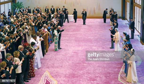 Emperor Akihito toast a glass with other royal family members and guests during a tea party to celebrate his 84th birthday at the Imperial Palace on...