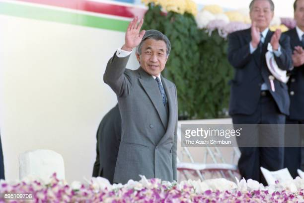 Emperor Akihito waves as he attends the opening ceremony of the National Sports Festival at Naruto Sports Park Athletic Stadium on October 24 1993 in...