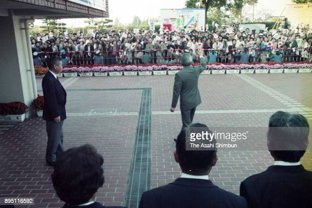 Emperor Akihito waves to wellwishers on arrival at the Marugame City Gymnasium to watch volleyball competition on October 26 1993 in Marugame Kagawa...