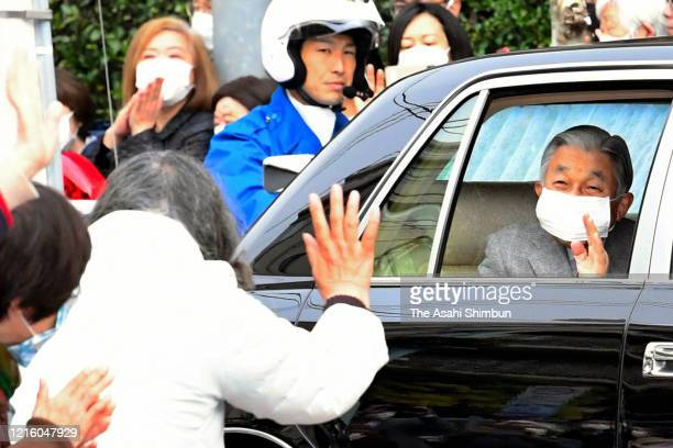 Emperor Emeritus Akihito wearing a face mask amid the coronavirus pandemic waves to well-wishers on arrival at their temporary home at the Takanawa...