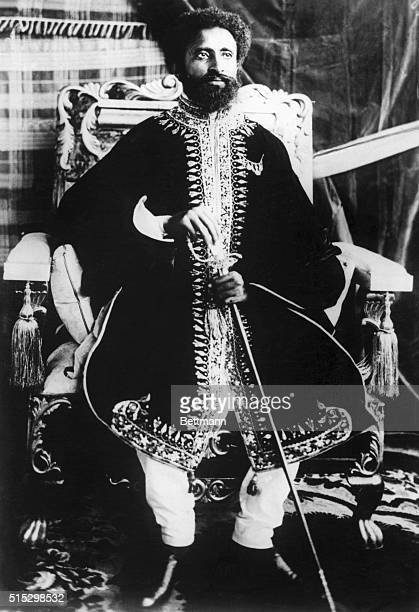 Emperor Haile Selassie holds a scepter and poses by his throne during his coronation