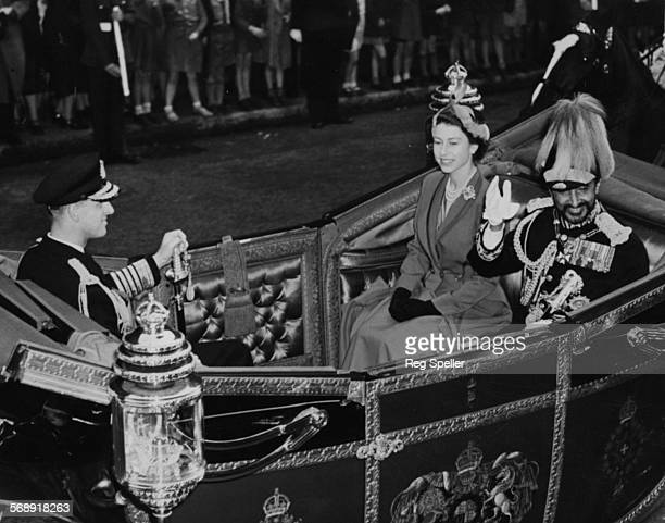 Emperor Haile Selassie waving as he rides in an open Landau carriage with Queen Elizabeth II and Prince Philip the Duke of Edinburgh during a state...