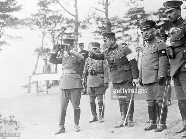 Emperor Hirohito looking through binoculars at the mimic war maneuvers which were held in November. One of his high military chiefs is explaining the...