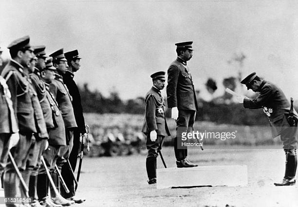 Emperor Hirohito of Japan receives a bow from the leader of a military unit during a troop review during World War II.
