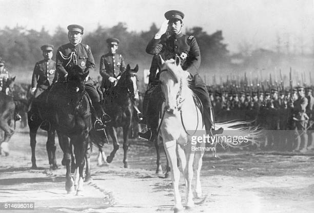 Emperor Hirohito salutes as he rides past and inspects his troops.