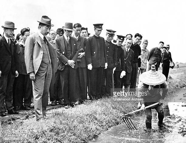 Emperor Hirohito visits the farming communities to learn first hand the problems they are having, Japan, March 19, 1948. Here he watches a farmer...