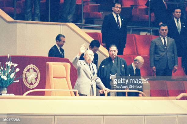 Emperor Hirohito waves to fans on day seven of the Grand Sumo Summer Tournament at Ryogoku Kokugikan on May 16 1987 in Tokyo Japan