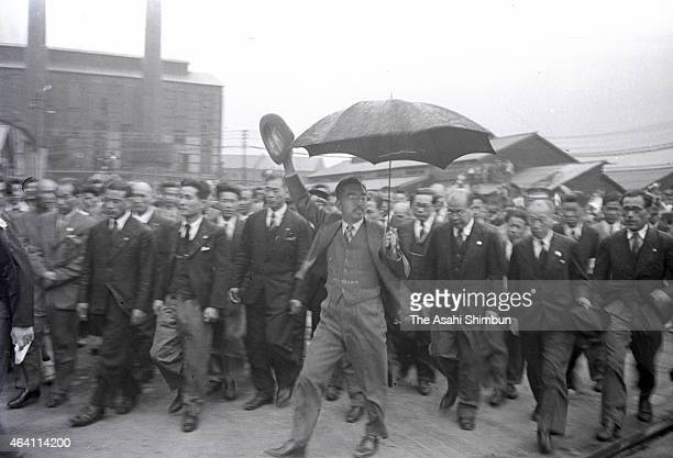 Emperor Hirohito waves to well-wishers as he inspects the Japan Iron and Steel Yahata Steel Yard during his visit to Kyushu on May 19, 1949 in...