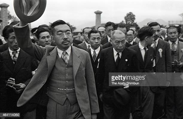 Emperor Hirohito waves to well-wishers as he inspects the Japanese Government Railways Kokura Train Depot during his visit to Kyushu on May 19, 1949...