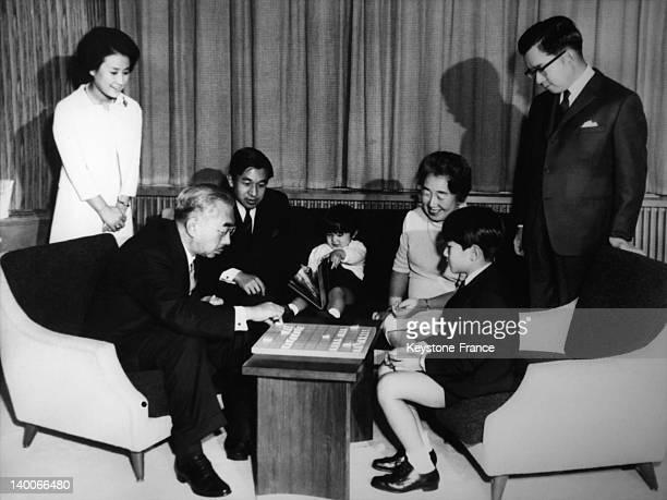 Emperor Hirohito with family during Christmas and New Year holiday Here he is playing shogi a Japanese chess game with grandson Prince Naruhito and...