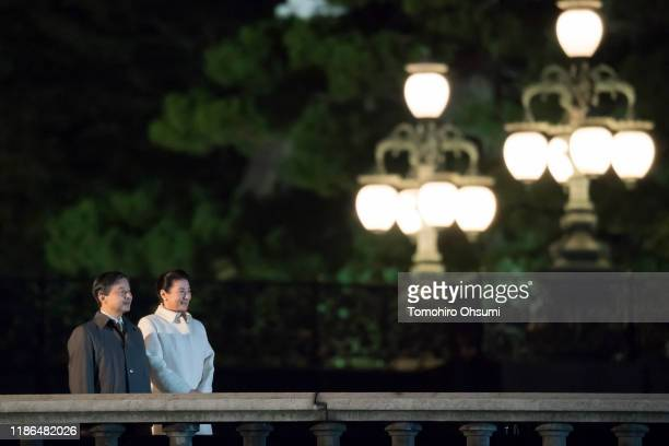 Emperor Naruhito and Empress Masako stand during the National Festival to Celebrate the Throne of New Emperor at the Imperial Palace at night on...