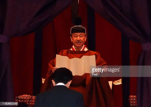 Emperor Naruhito speaks near Japan's Prime Minister Shinzo Abe during a ceremony to proclaim his enthronement to the world, called...