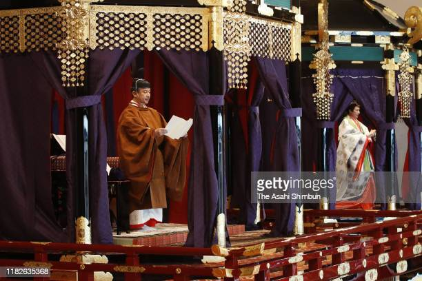 "Emperor Naruhito stands on the ""takamikura"" platform while Empress Masako stands on the ""michodai"" structure set up in the Matsu-no-Ma state room..."