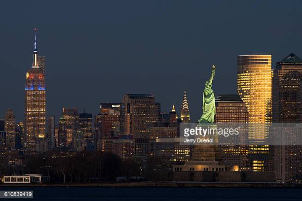 Empire State and Statue of Liberty at dusk.