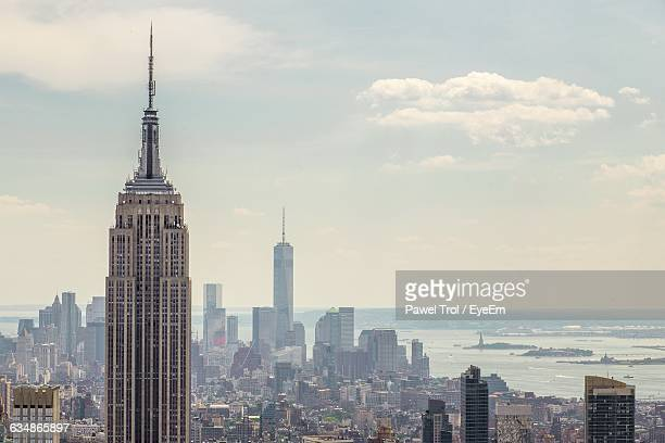 empire state building against towers at manhattan - empire state building stock pictures, royalty-free photos & images