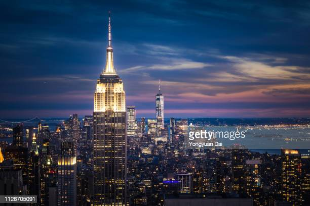 empire state building and new york city skyline at night - new york city stockfoto's en -beelden
