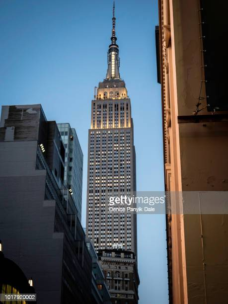 empire state building at dusk clear blue sky background - panyik-dale stock photos and pictures