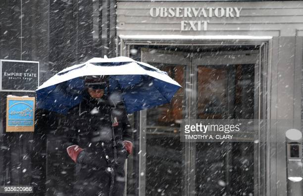 Empire State Building doorman in the snow on 5th Avenue in New York March 21 2018 as the fourth nor'easter in a month hits the tristate area on the...