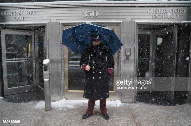 TOPSHOT Empire State Building doorman weathers the snow in New York on March 21 as the fourth nor'easter in a month hits the tristate area on the...