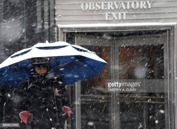 Empire State Building doorman weathers the snow in New York on March 21 as the fourth nor'easter in a month hits the tristate area on the first full...