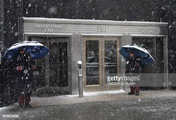 Empire State Building doormen weather the snow in New York on March 21 as the fourth nor'easter in a month hits the tristate area on the first full...